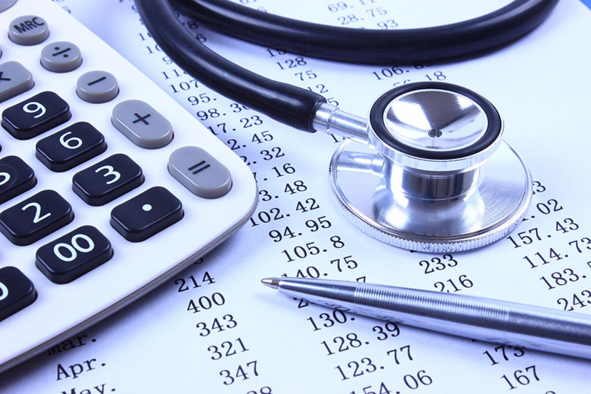 stock photo showing a calculator and a stethoscope on top of a balance sheet