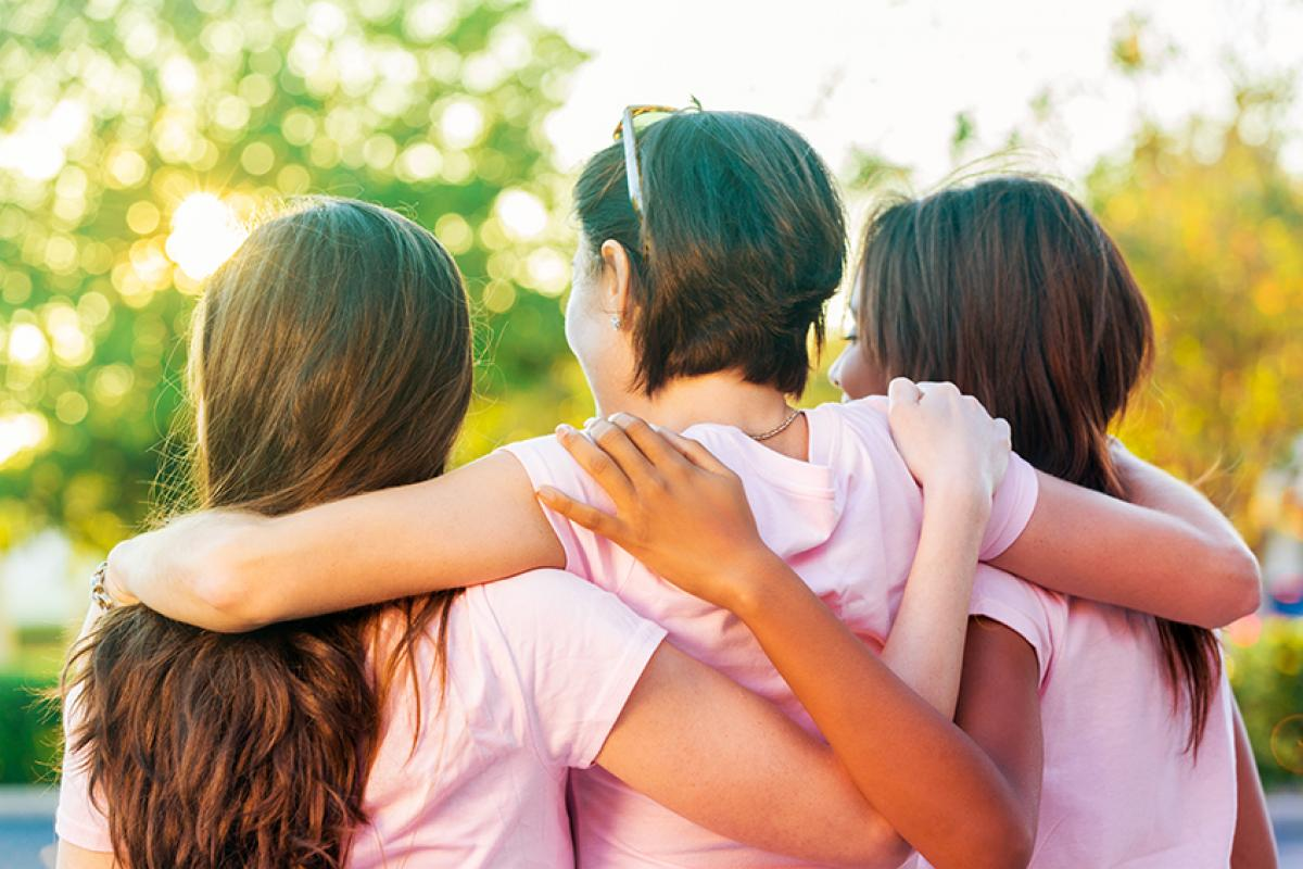 photo of the backs of three young women with their arms around each other